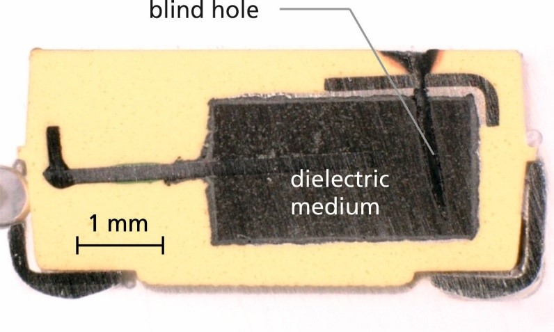 Cross section of a tantalum capacitor. The arrow indicates the blind hole generated by laser ablation to access the dielectric medium.