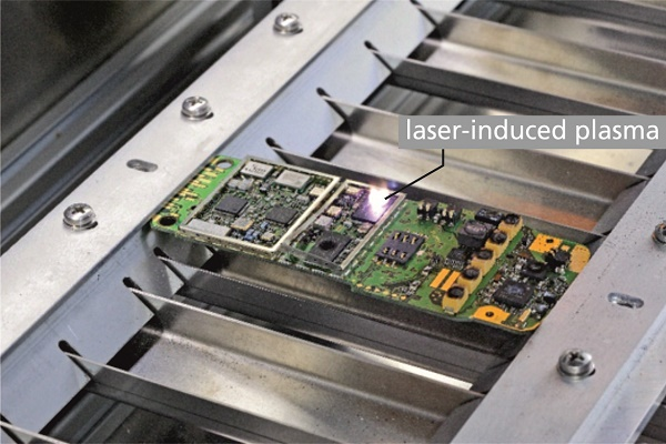 Printed circuit board of a mobile phone clamped in machine 5 while a laser spectroscopic measurement at an electronic component is conducted, see bright spot of laser-induced plasma.